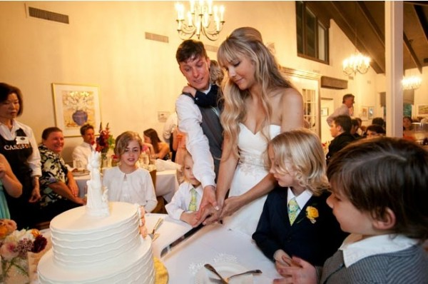 Cute newly weds cut the cake at Casa Garden Wedding Venue