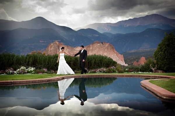 Reflection of wedded couple in front of Garden of the Gods and Rocky Mountains